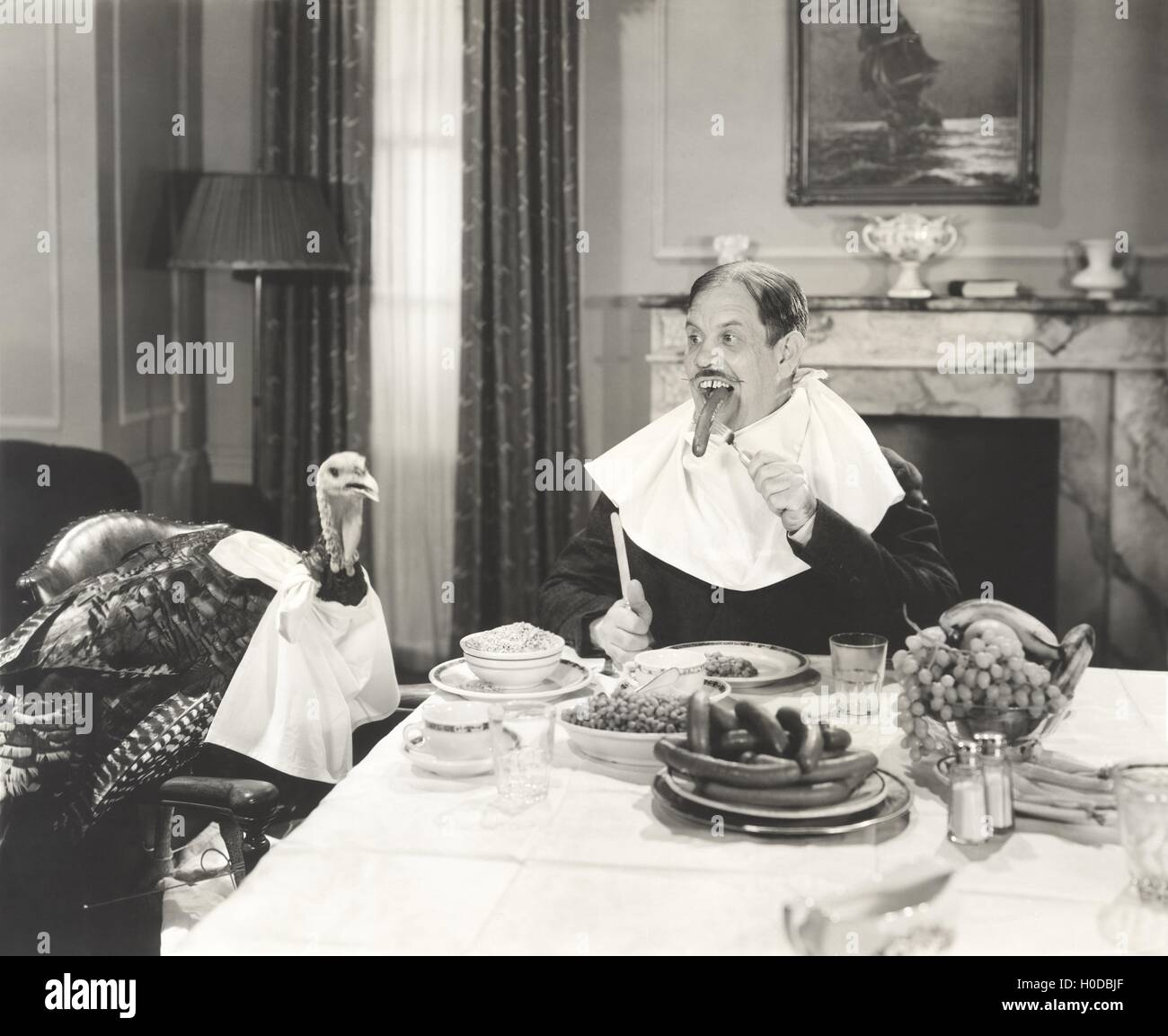 Man and his pet turkey sitting down to an untraditonal Thanksgiving dinner - Stock Image