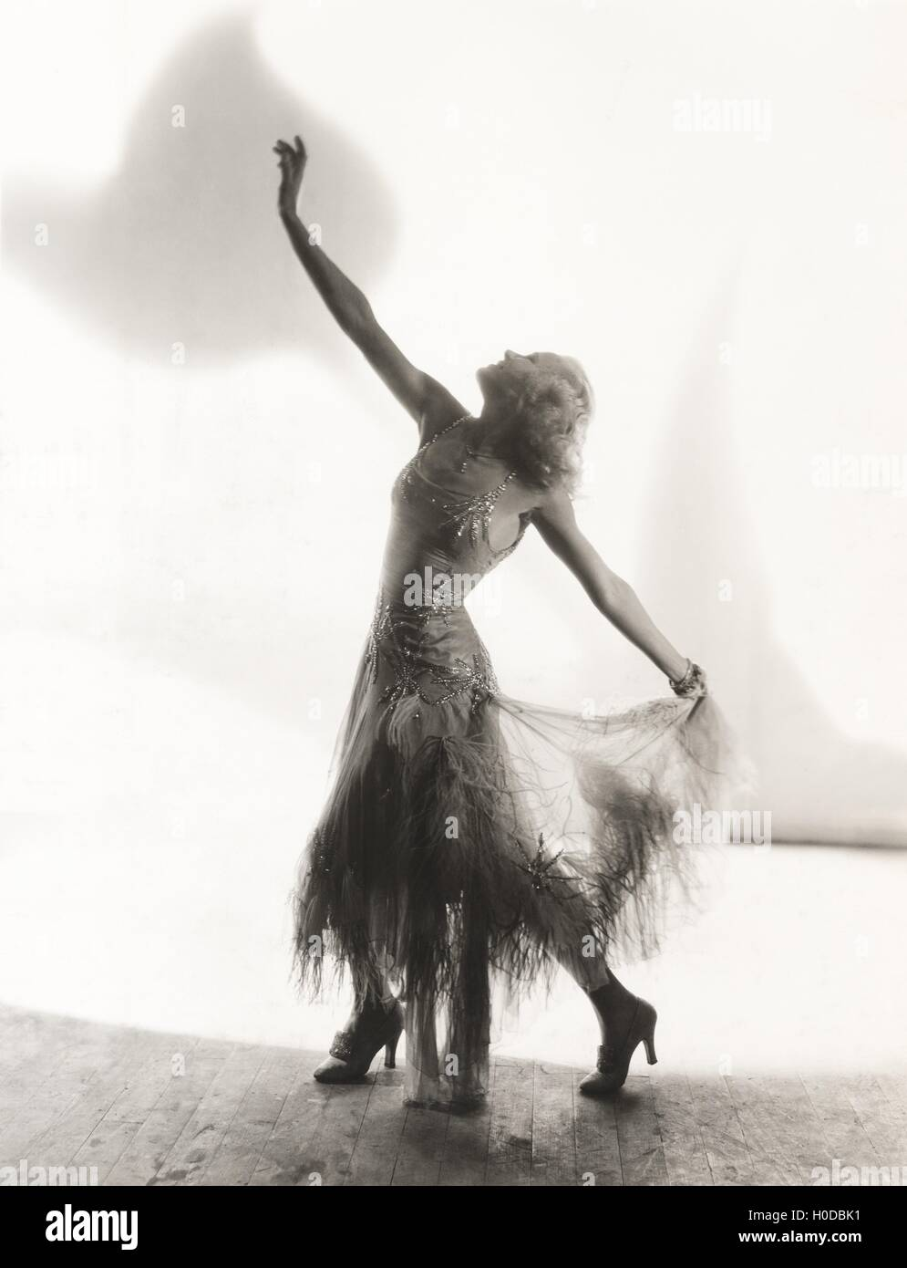 Dancer with arms outstretched against white background - Stock Image