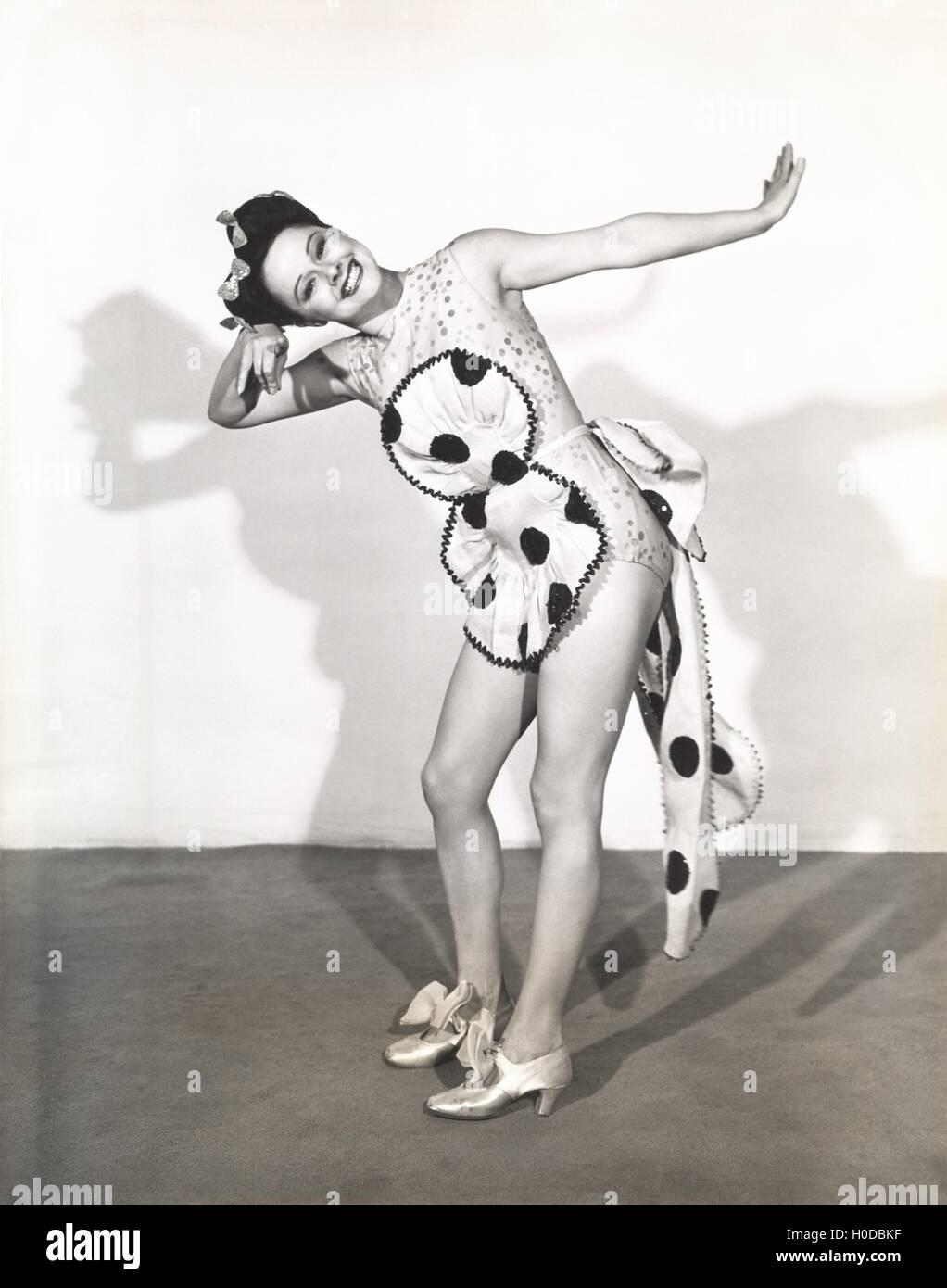 Dancer posing in polka dot apron Stock Photo