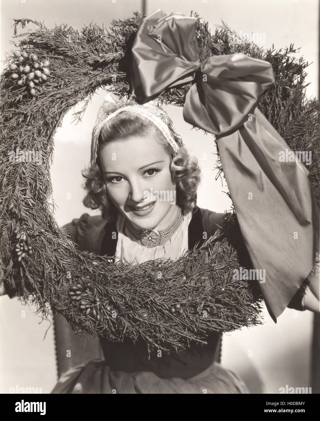 Woman holding large Christmas wreath with bow Stock Photo