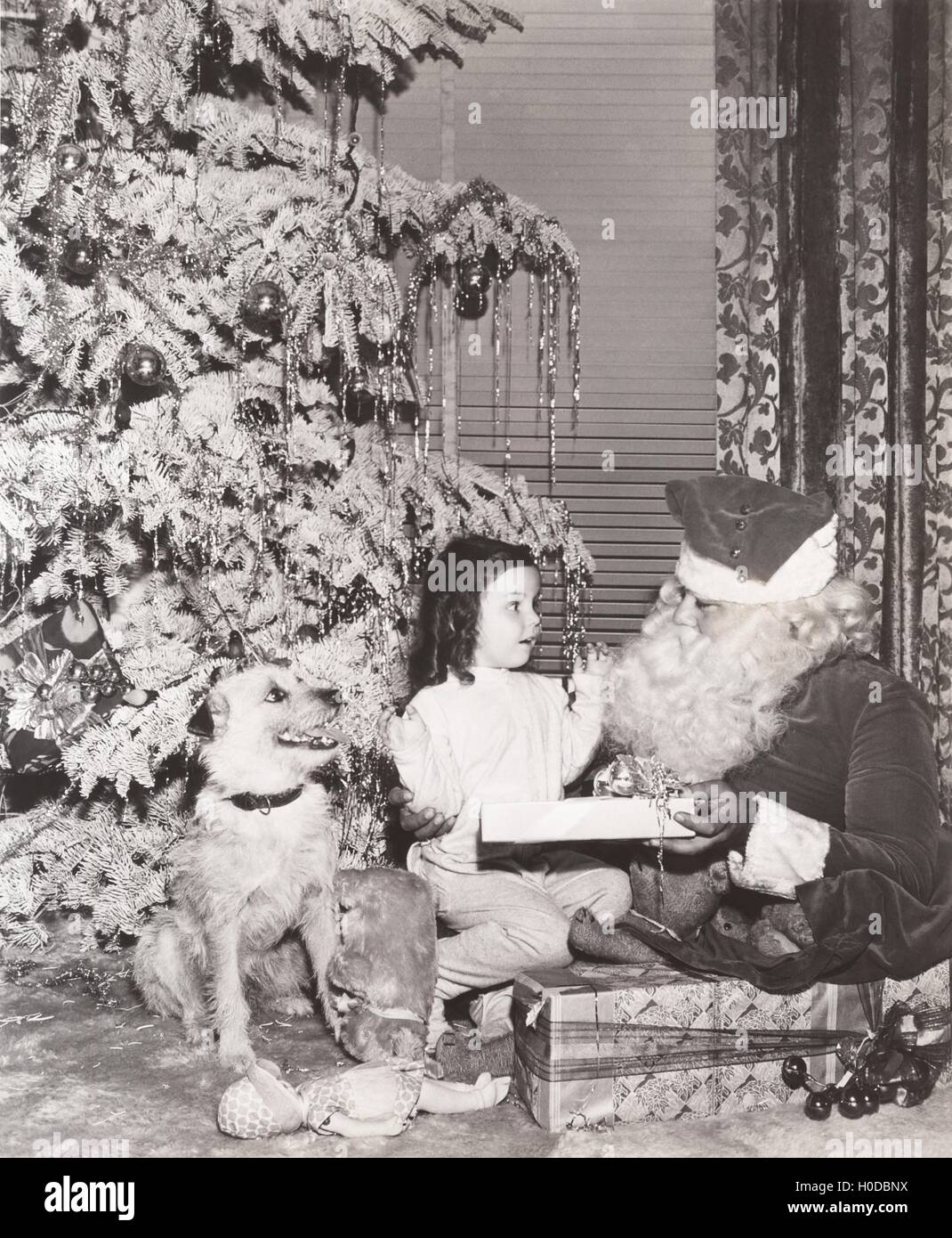 Santa Claus giving gift to little girl and her dog Stock Photo