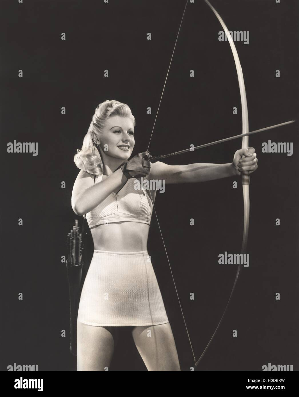 Woman in crop top and mini skirt shooting bow and arrow - Stock Image