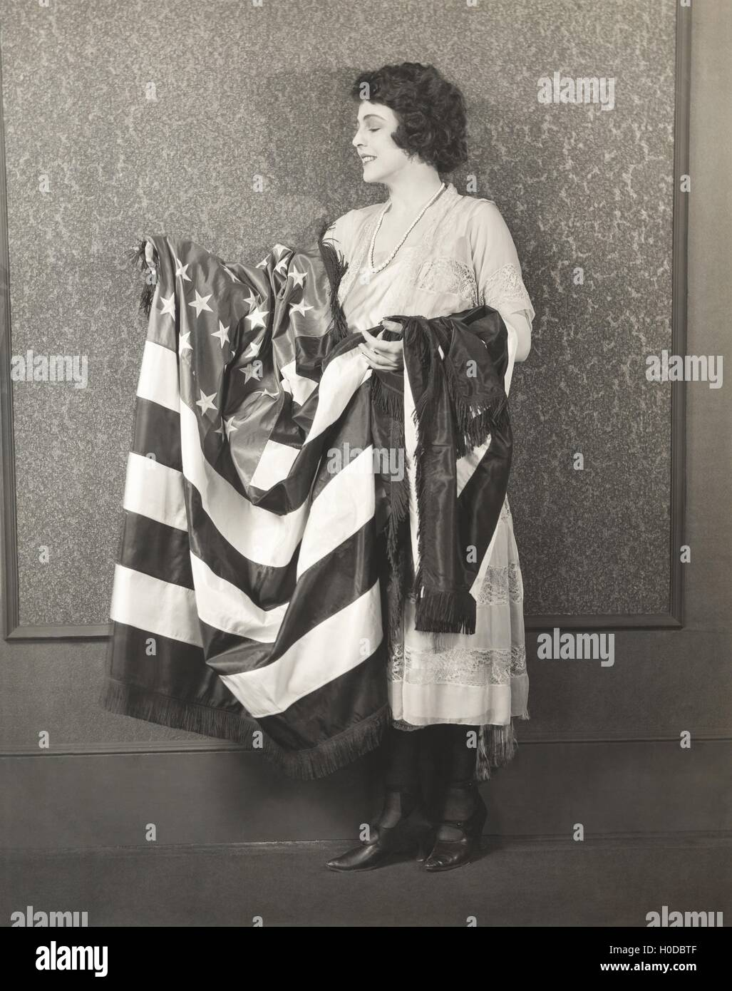 Woman with draped American flag over her arms - Stock Image