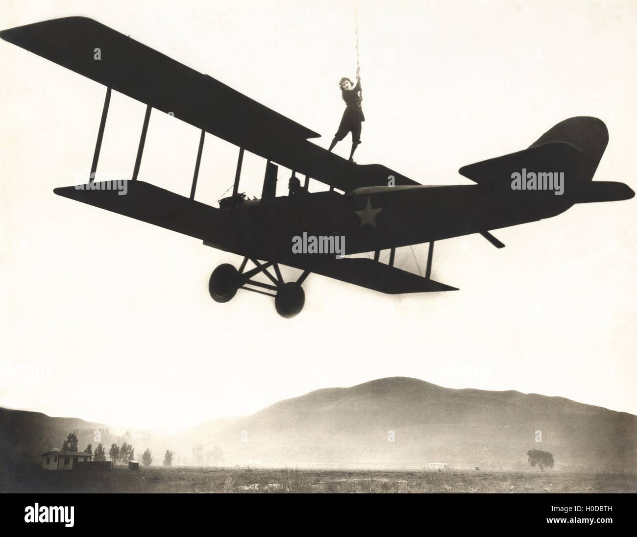 Stunt woman standing on top of biplane Stock Photo