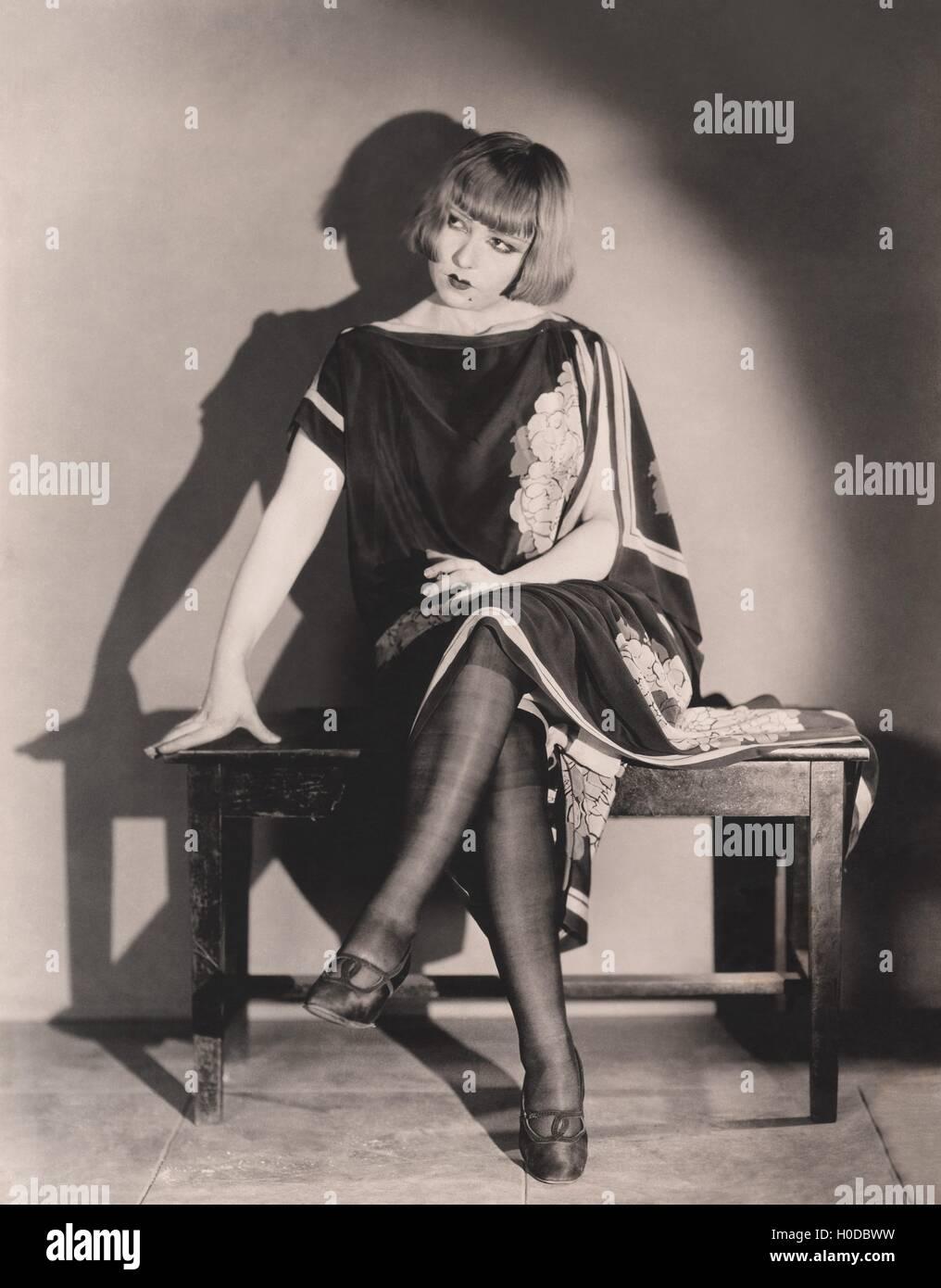 Fashionable woman sitting on piano bench Stock Photo