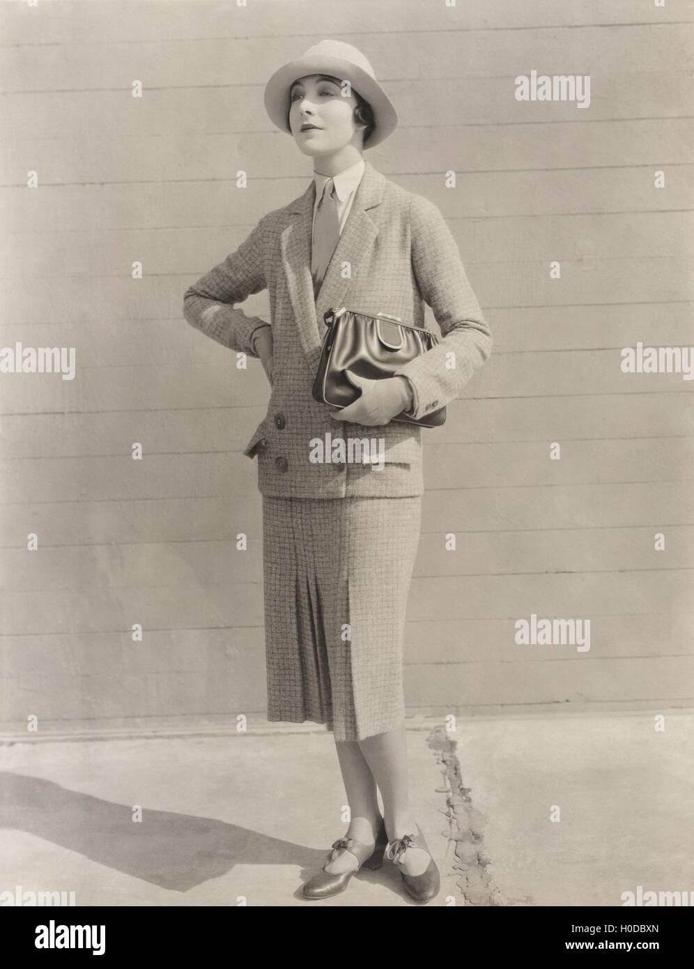 Woman in skirt suit carrying handbag - Stock Image