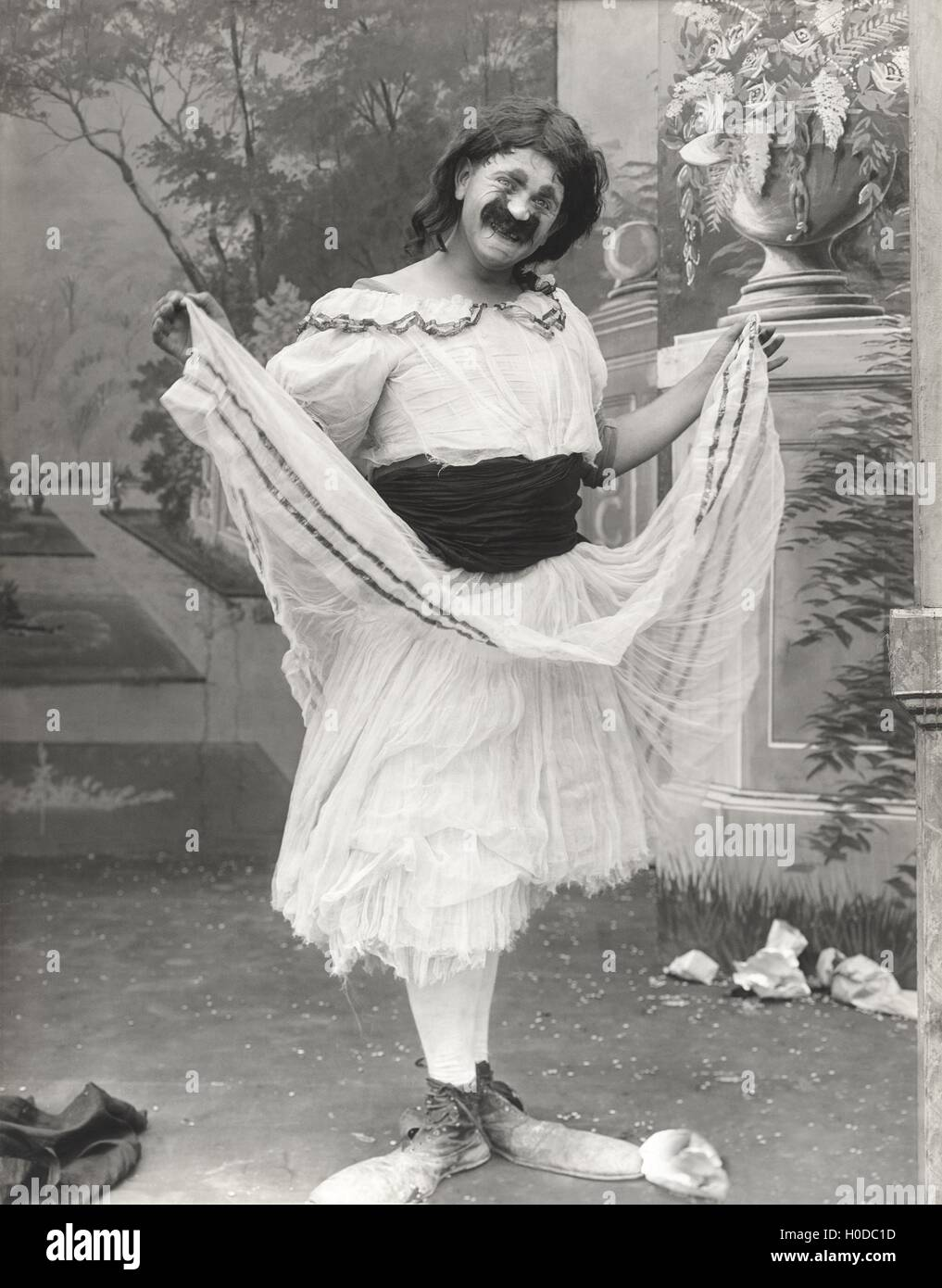 Man in clown shoes dressed in drag - Stock Image