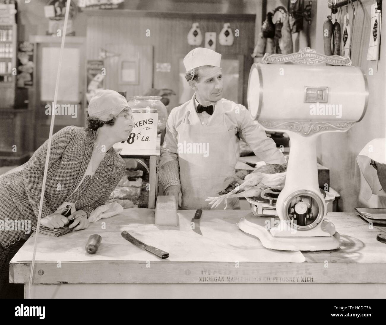 Butcher and customer looking at weight of chicken on scale - Stock Image