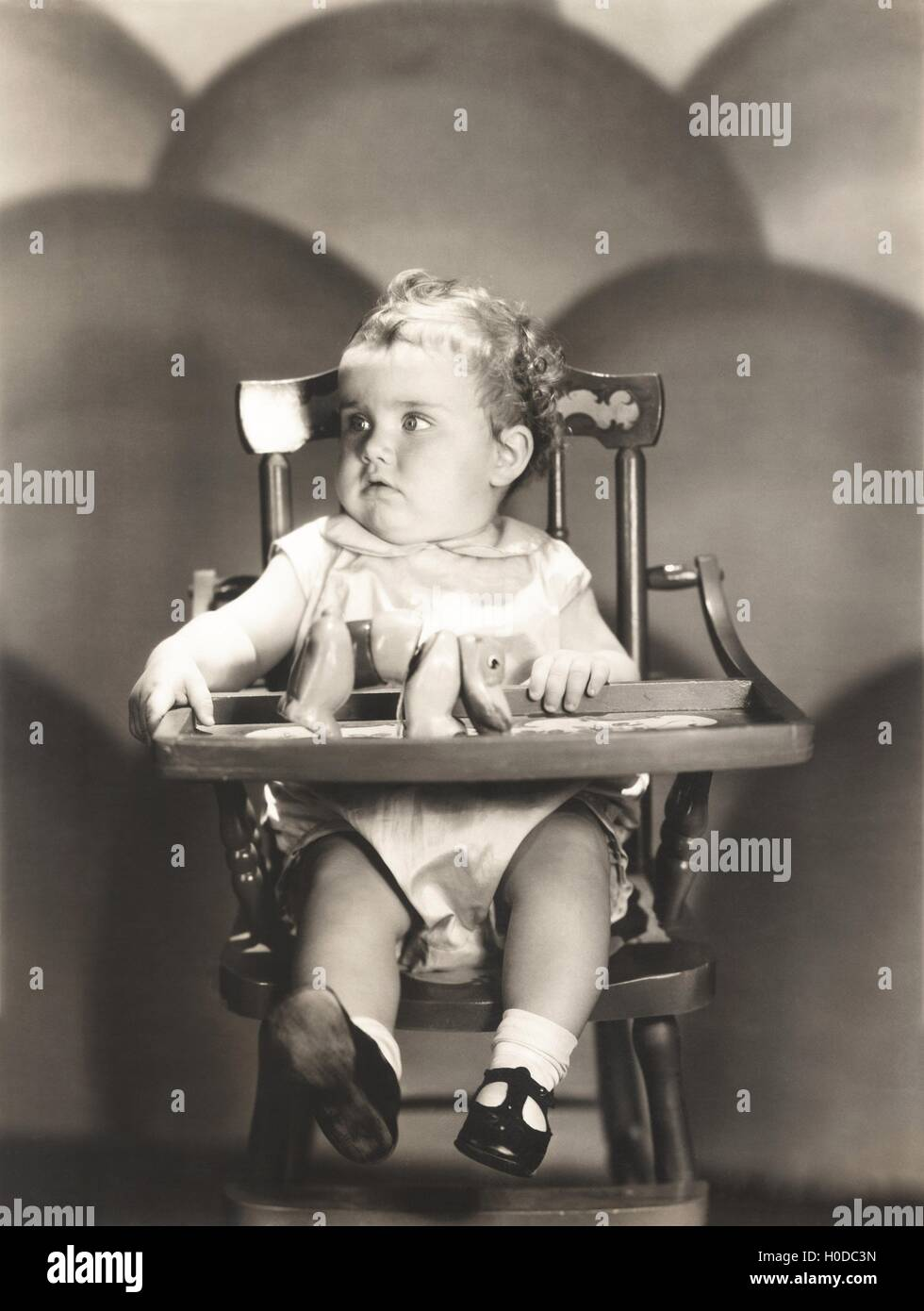 Cute baby sitting on high chair - Stock Image