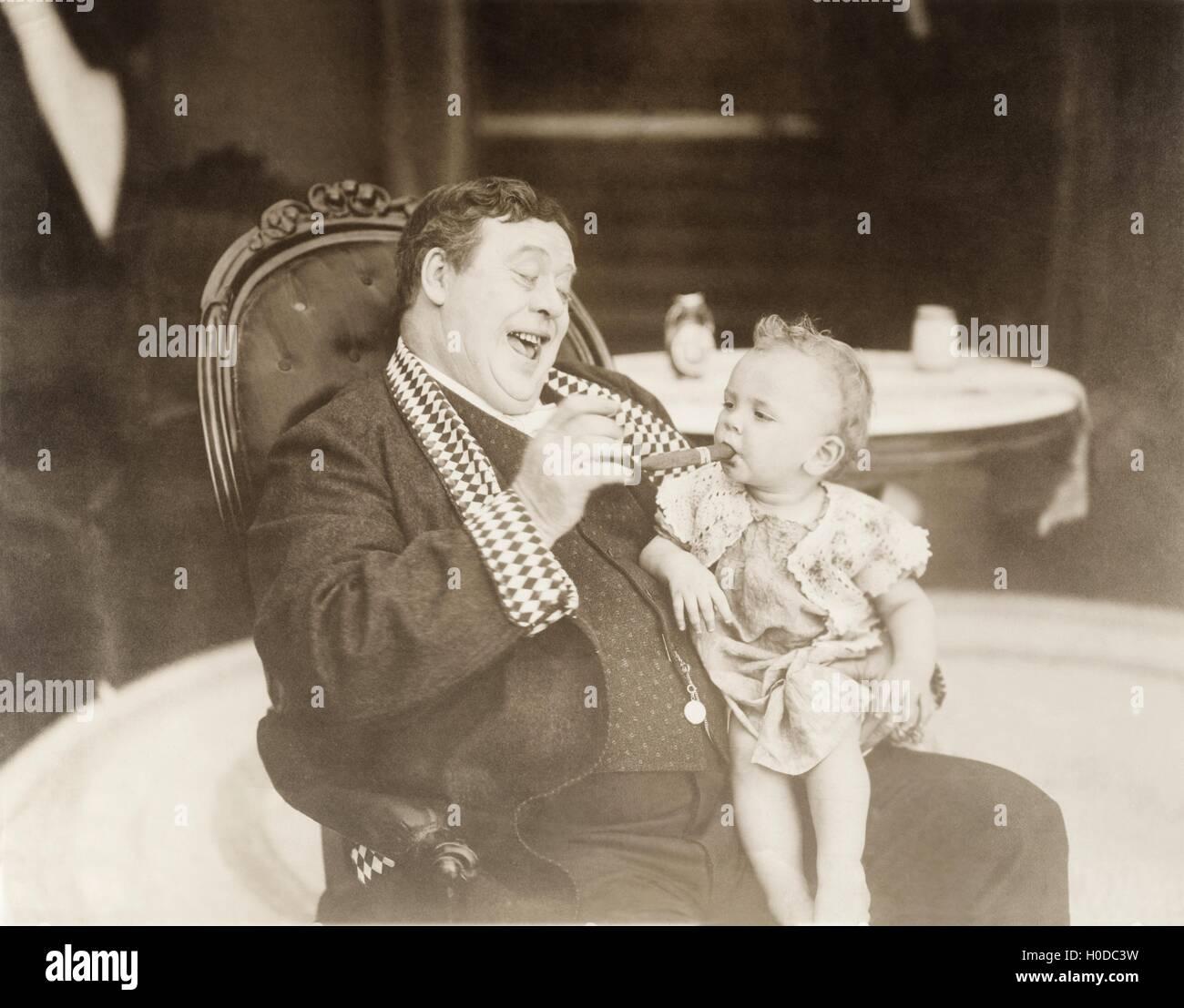 Man laughing at baby smoking cigar - Stock Image