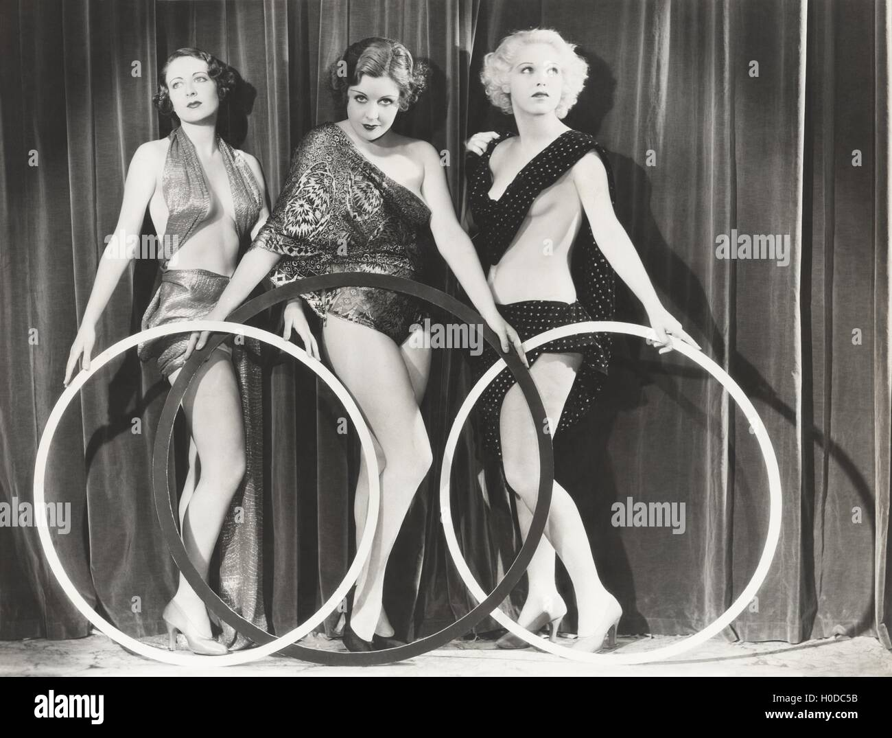 Three scantily clad women holding large rings - Stock Image
