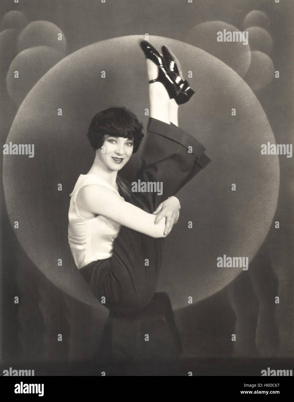 Woman holding her legs up in the air, 1930s - Stock Image