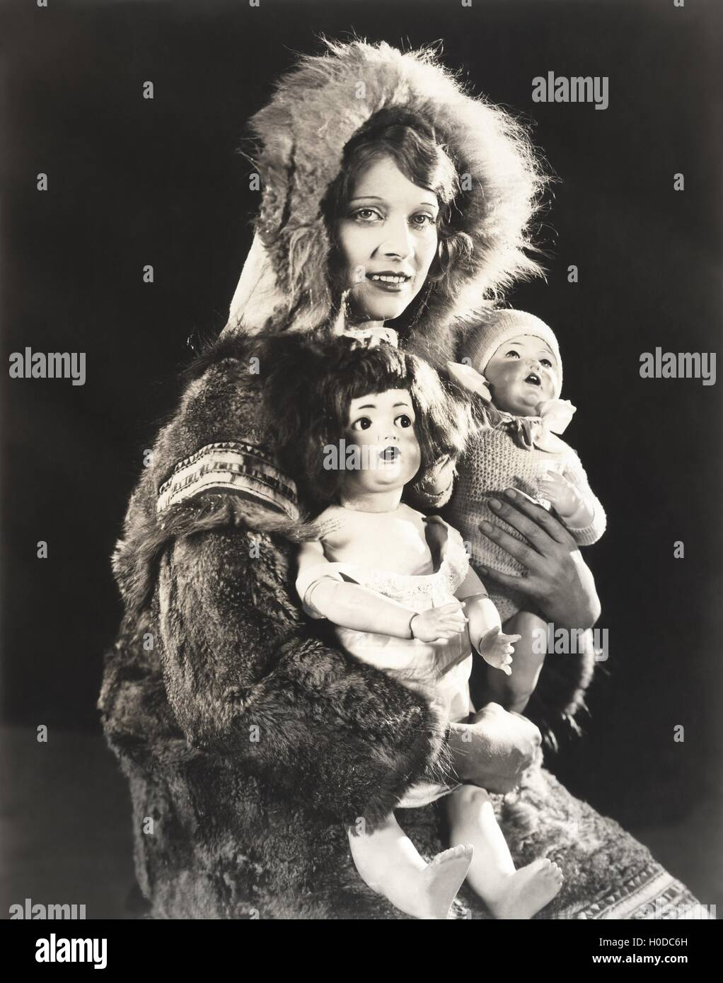 Women wearing Eskimo fur coat holding dolls - Stock Image
