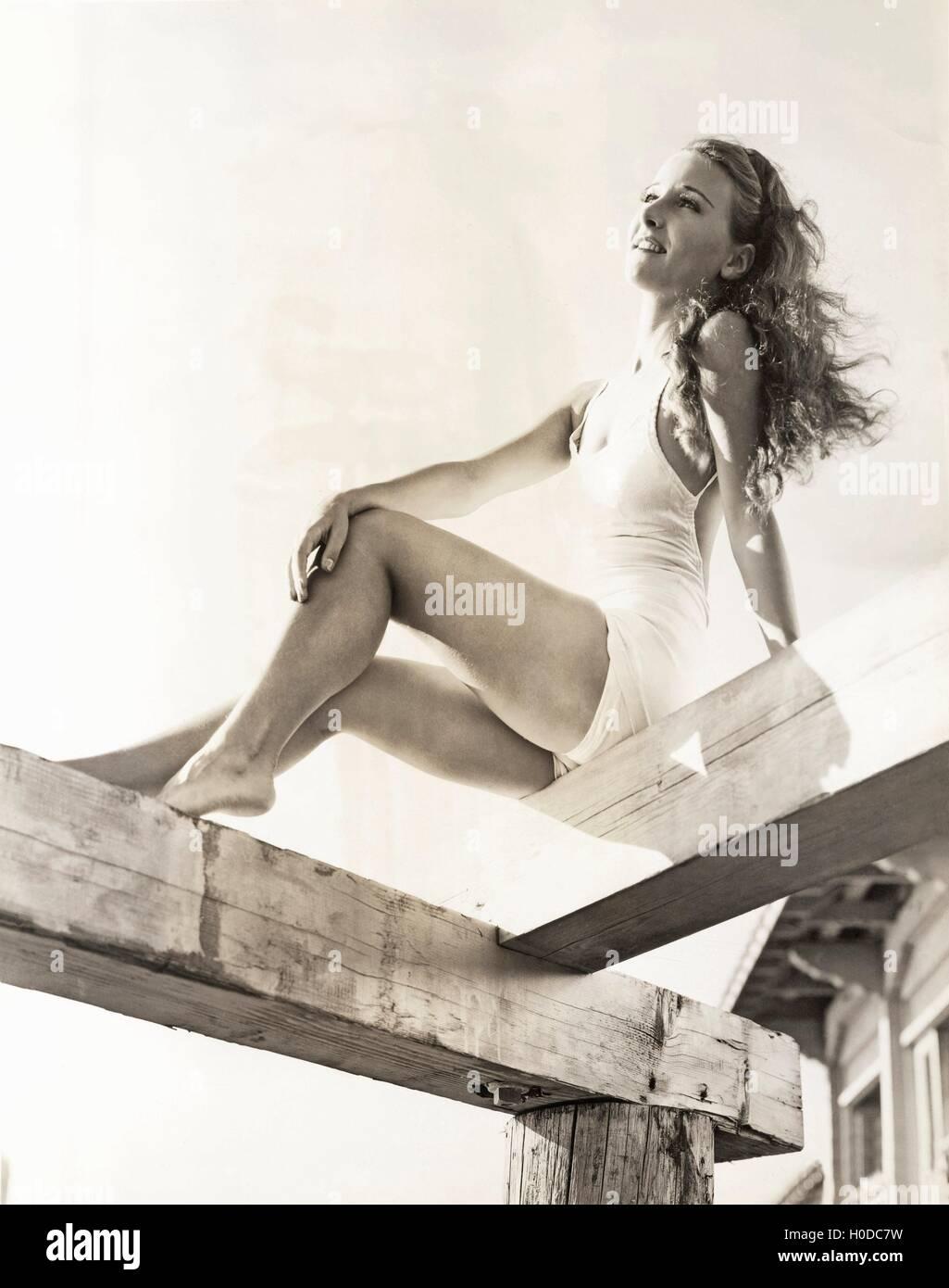 Woman sunbathing on a pier - Stock Image