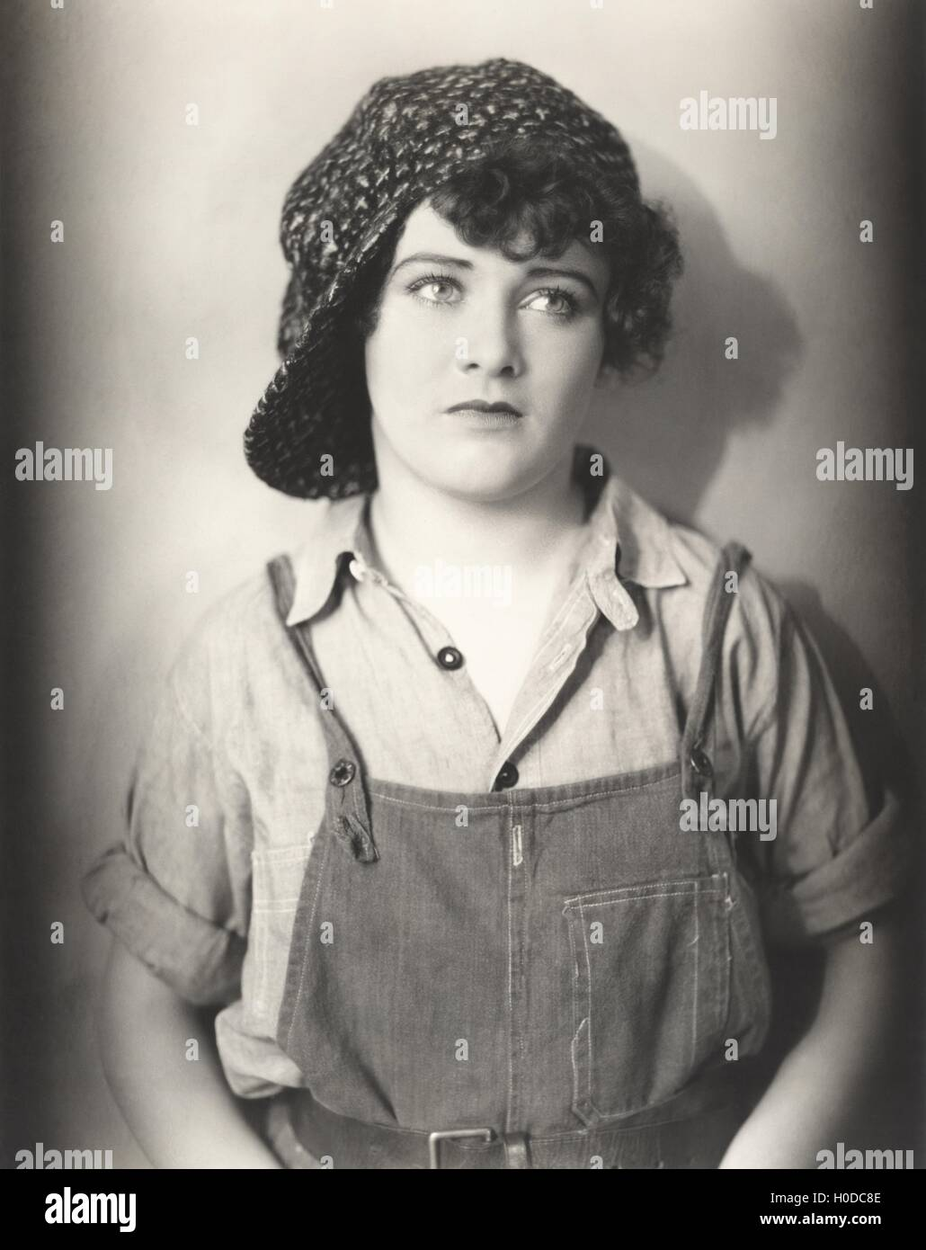 Woman in backwards cap and bib overalls - Stock Image