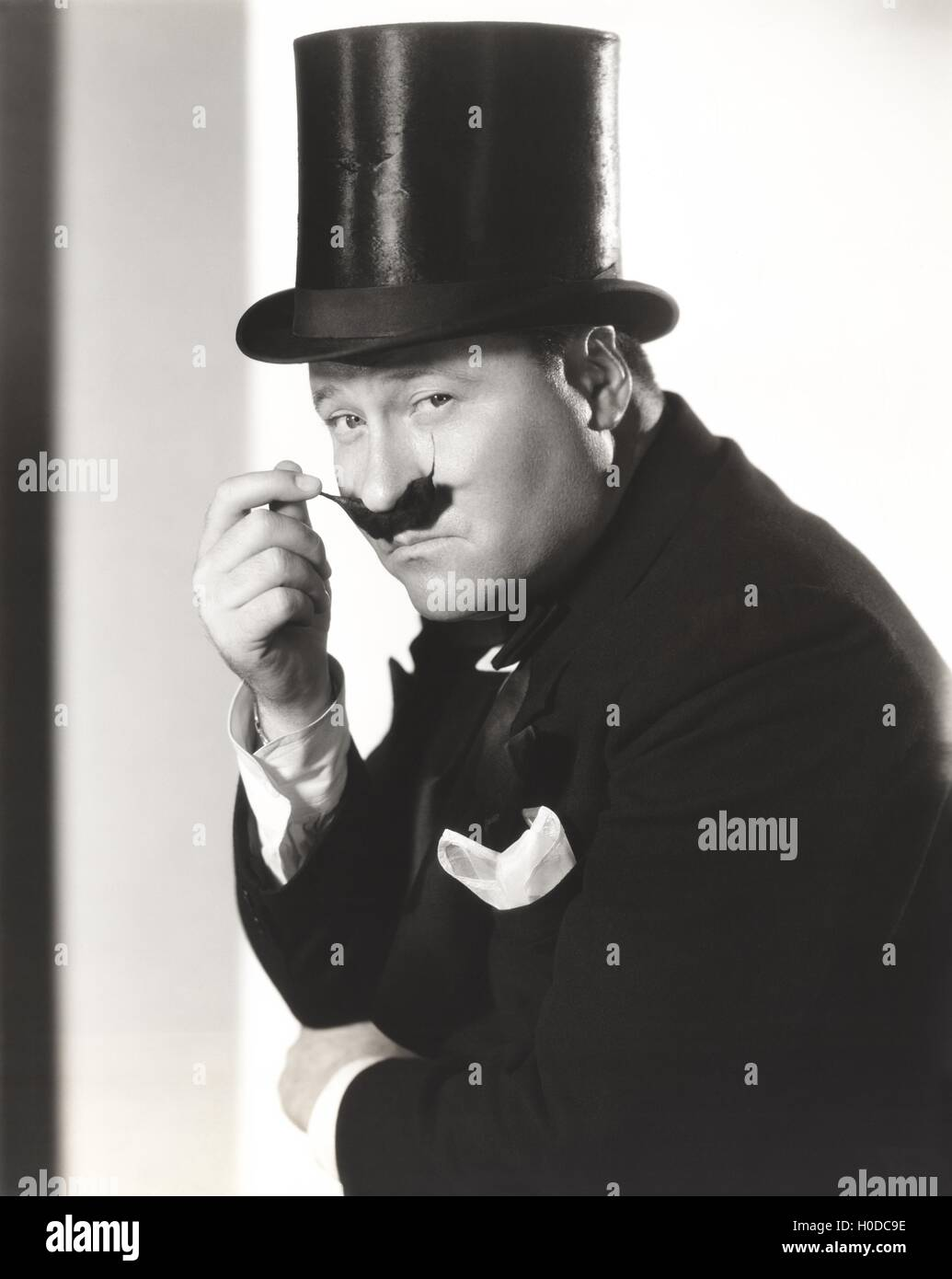 Man in top hat with waxed mustache - Stock Image