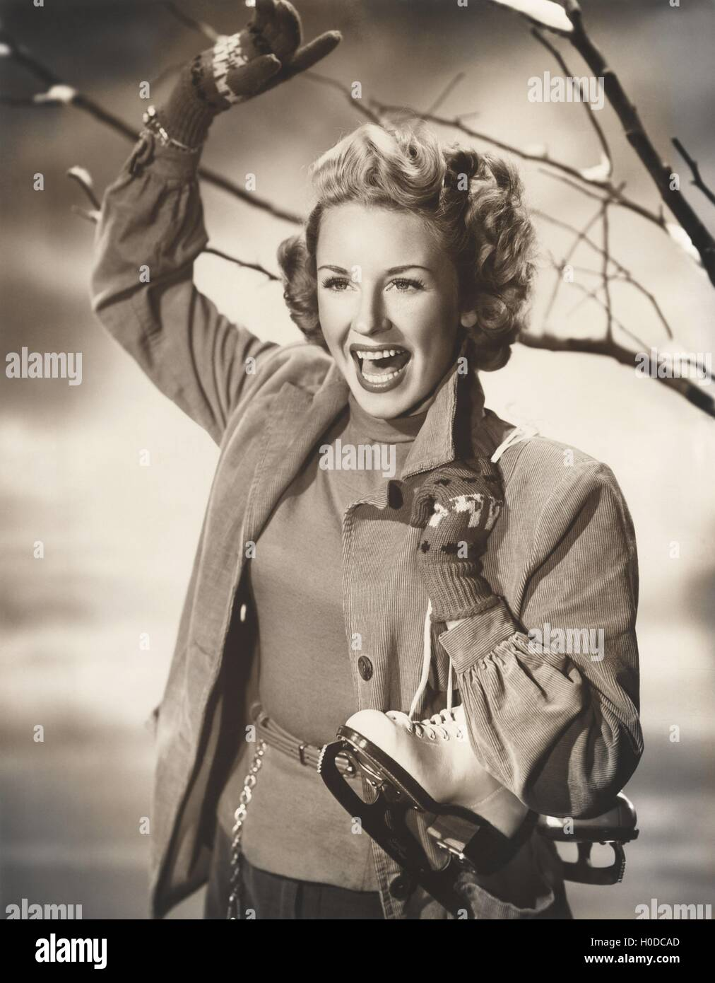 Happy woman carrying ice skates - Stock Image