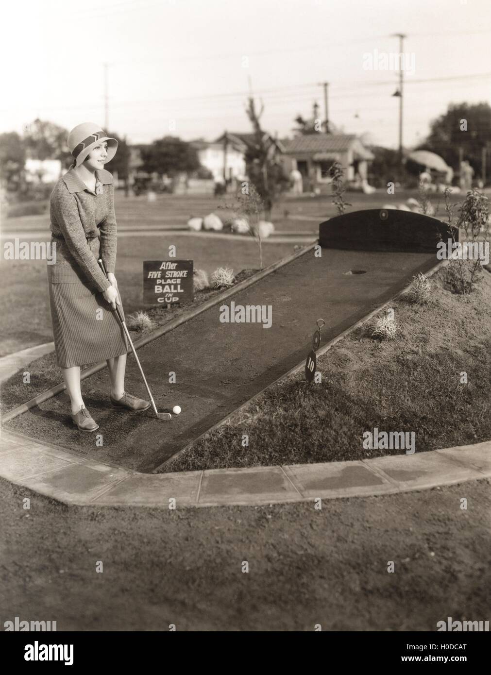Enjoying a solo game of miniature golf - Stock Image