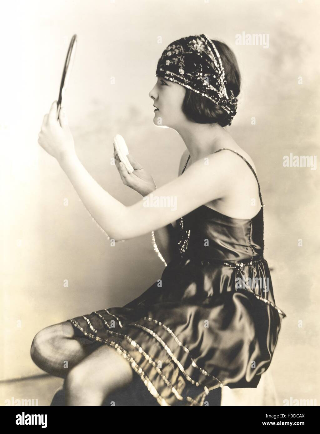 Side view of young woman holding powder puff and mirror - Stock Image