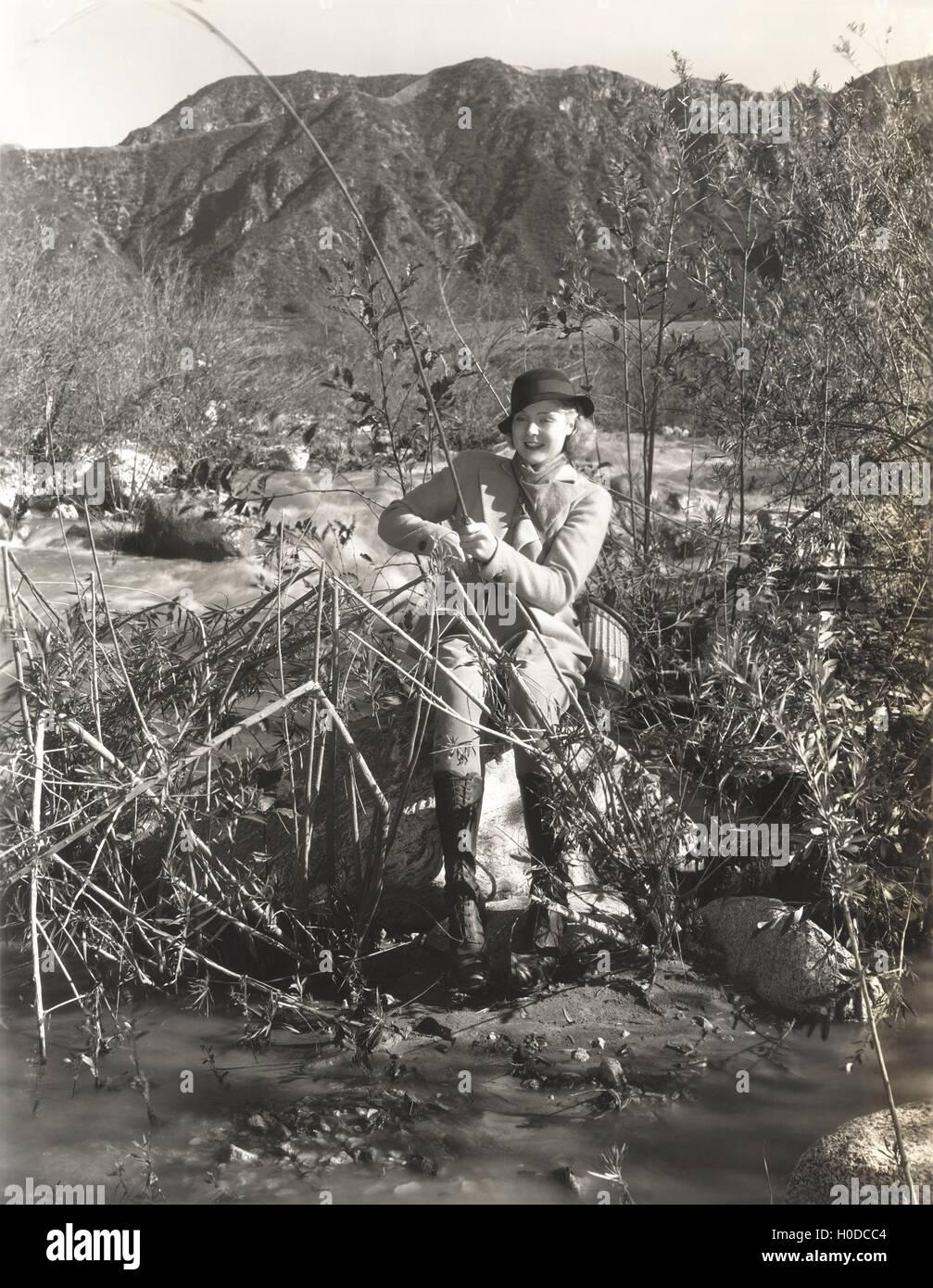 Woman fishing on a river bank - Stock Image