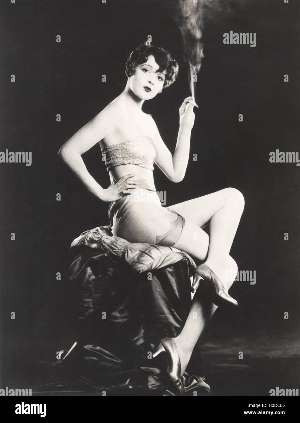 Scantily clad woman holding lit cigarette - Stock Image