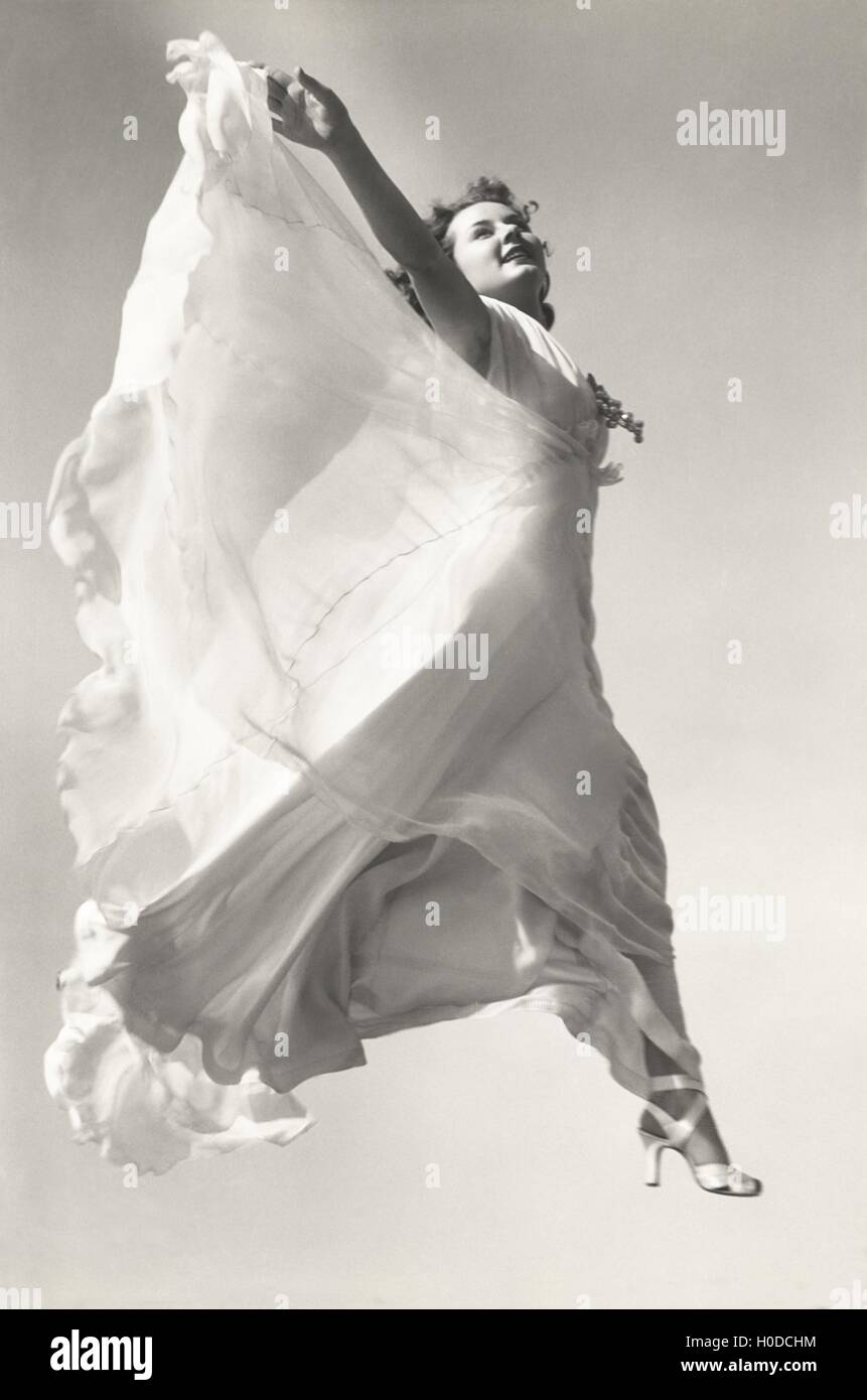 Low angle view of woman in gown jumping in mid-air - Stock Image
