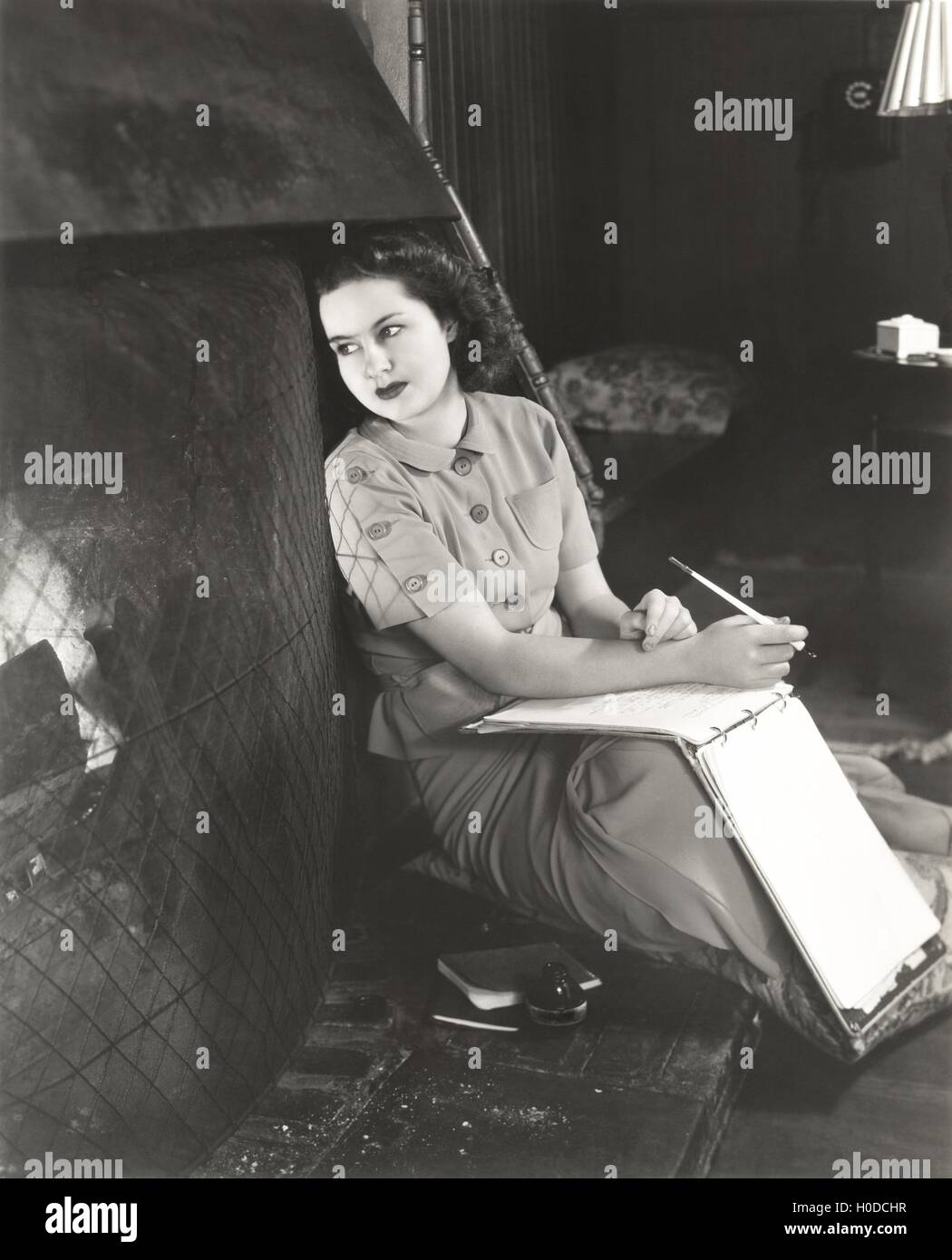 Woman with notebook daydreaming by fireplace - Stock Image