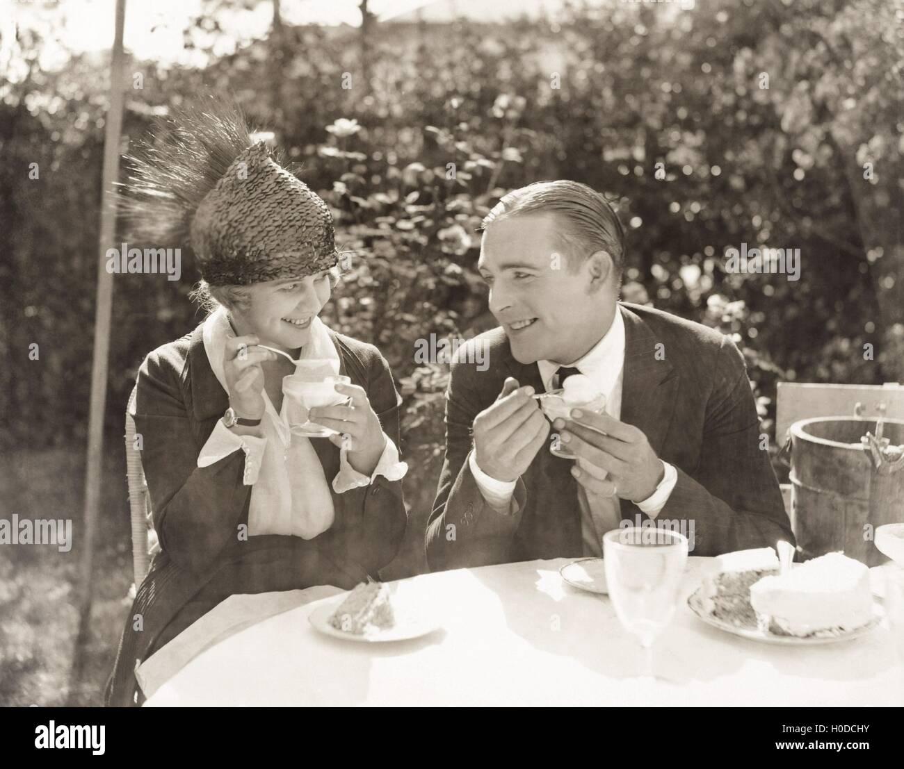 Couple eating ice cream and cake - Stock Image