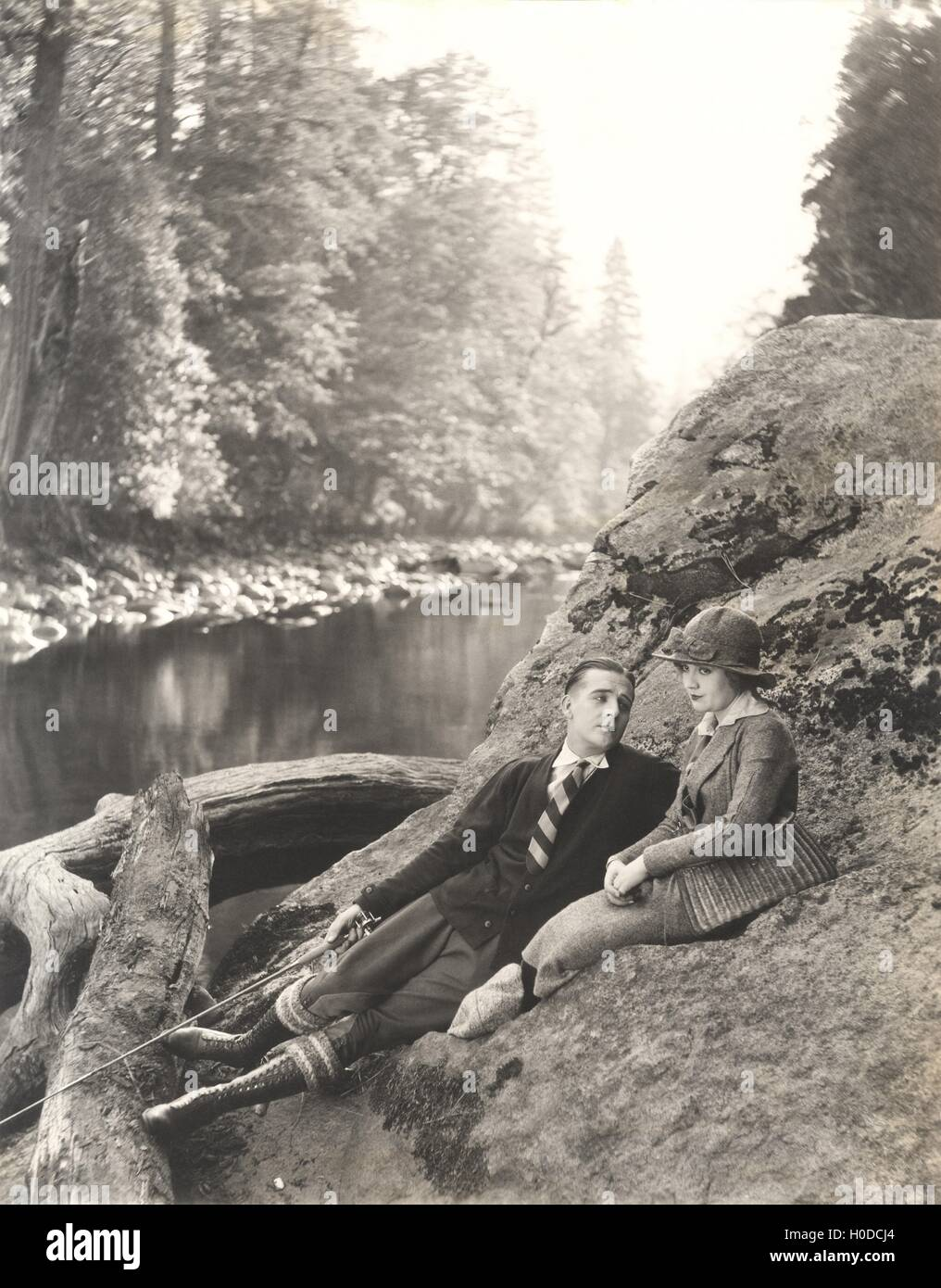 Couple sitting on rock beside stream - Stock Image
