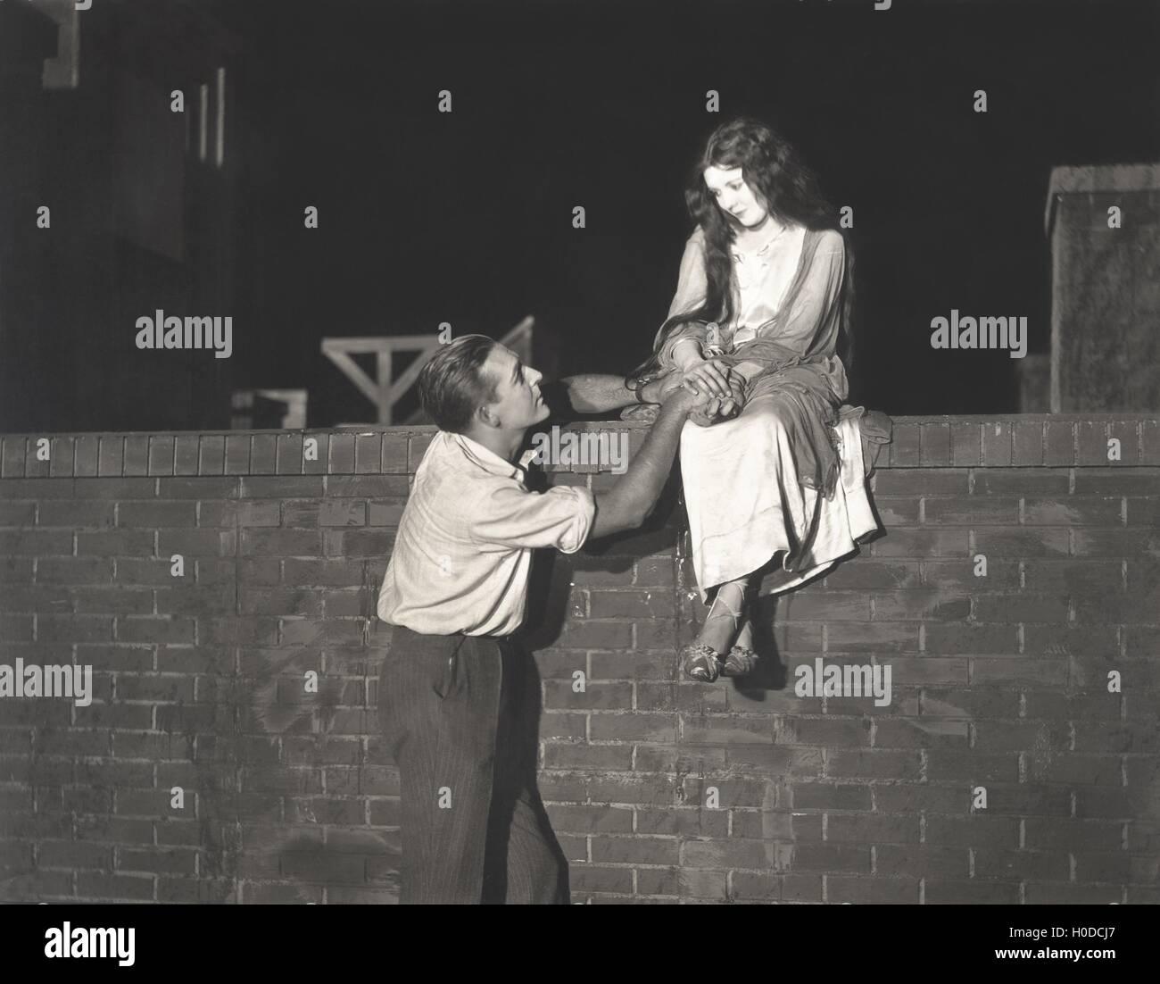 Man wooing woman sitting on brick wall - Stock Image