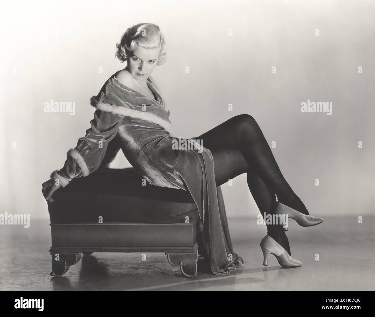 Woman in velvet dress sitting on footstool - Stock Image