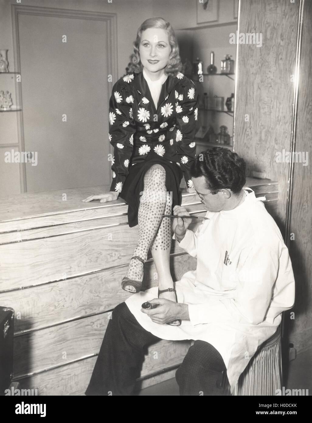 Makeup artist painting stockings on woman's legs - Stock Image
