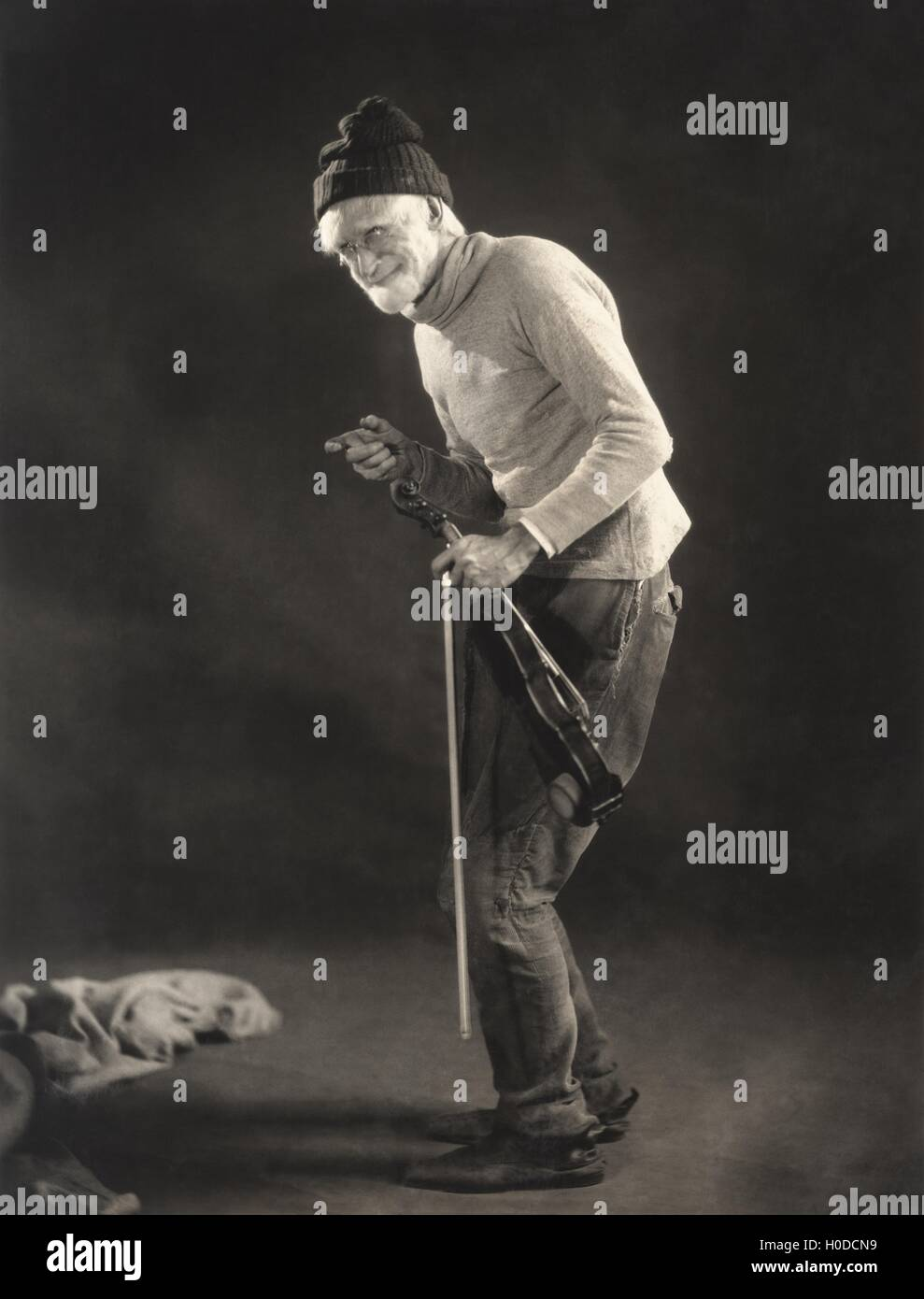 Senior man in woolen cap holding a violin - Stock Image