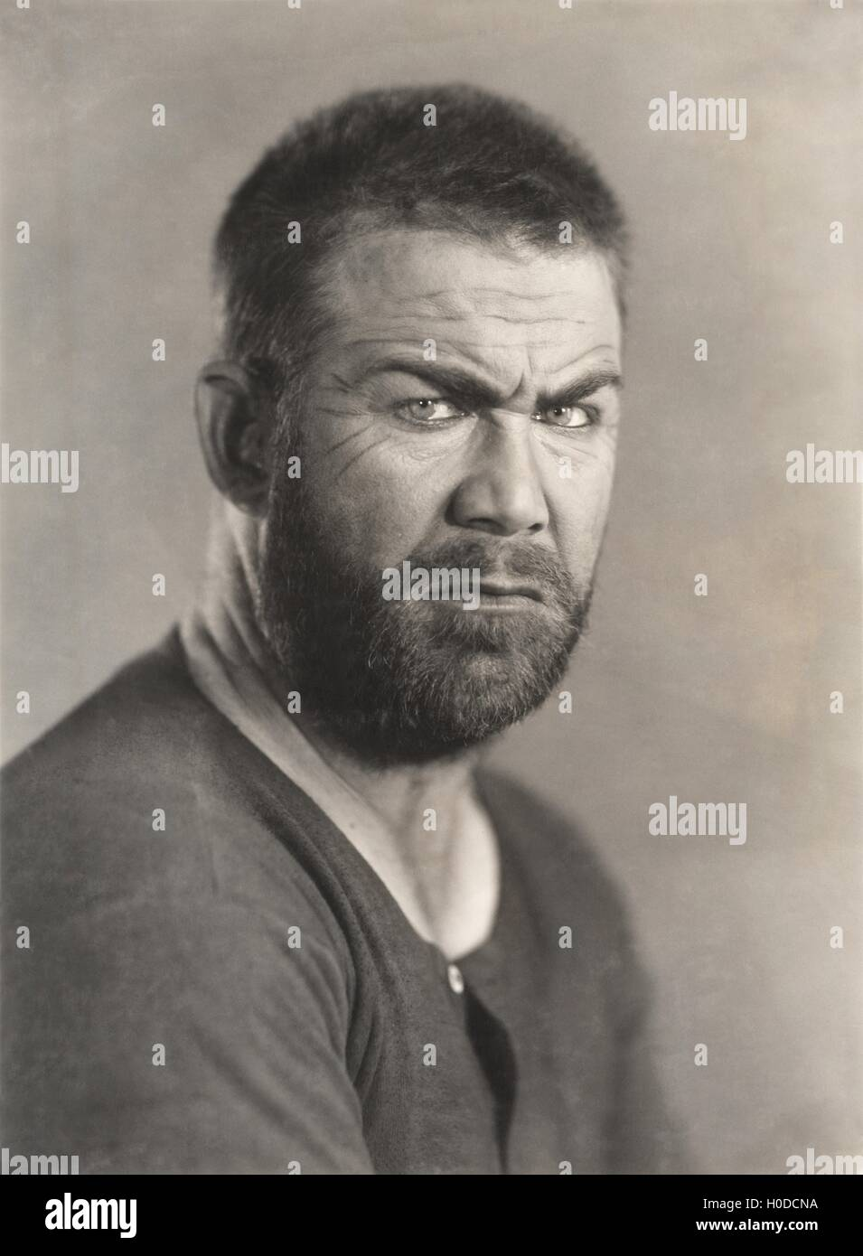 Portrait of a frowning bearded man - Stock Image