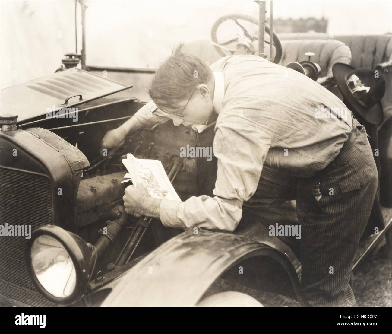 Man reading instructions on how to fix car - Stock Image