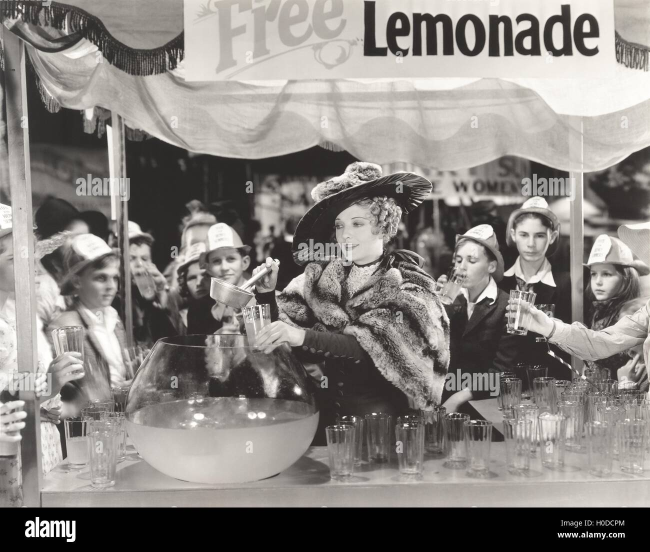 Woman giving out free lemonade to children at fair - Stock Image