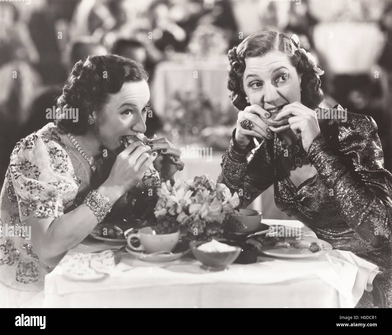 Two women distracted from their meal - Stock Image