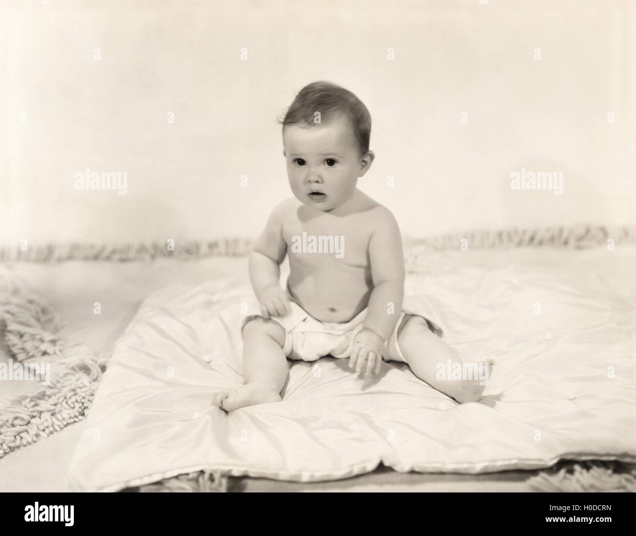 Portrait of baby girl sitting on blanket - Stock Image