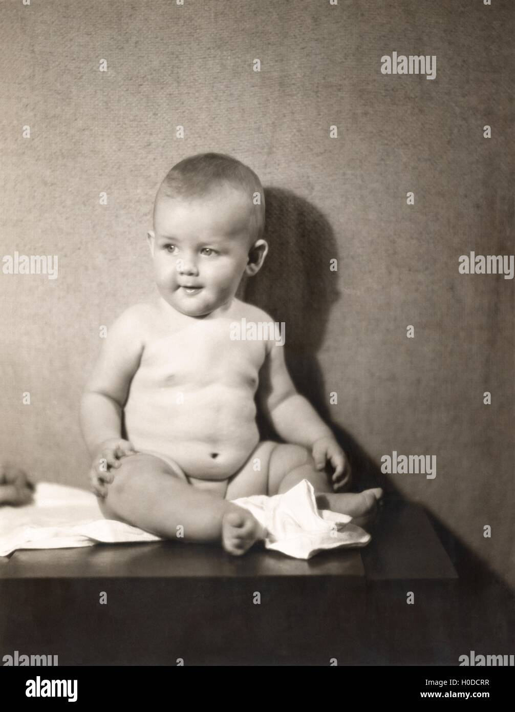 Chubby baby boy sitting on table with diaper off - Stock Image