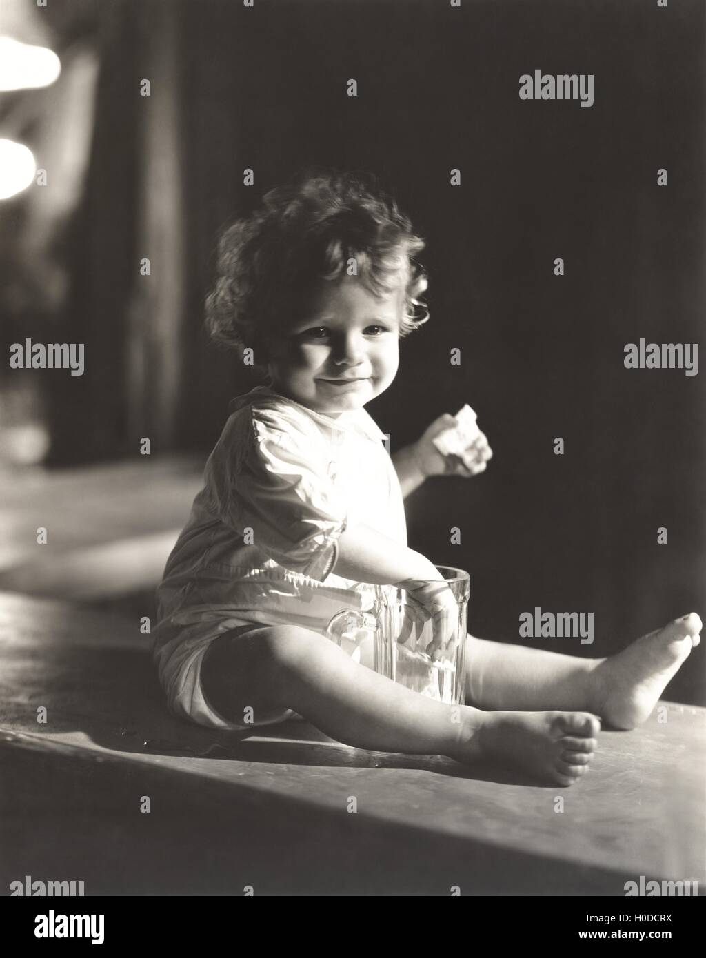 Baby boy with his hand in a beer glass - Stock Image