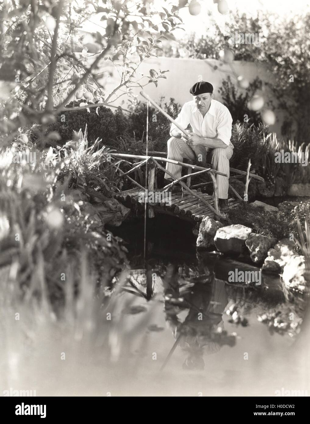 Man sitting on footbridge fishing in pond - Stock Image