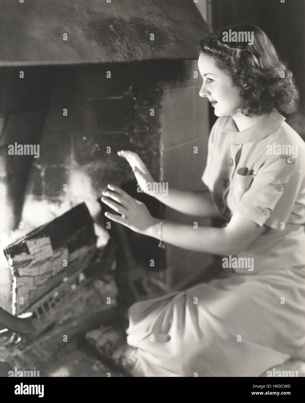 Woman warming her hands by the fireplace - Stock Image