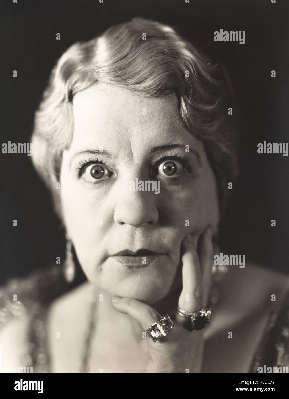 Portrait of wide-eyed woman - Stock Image