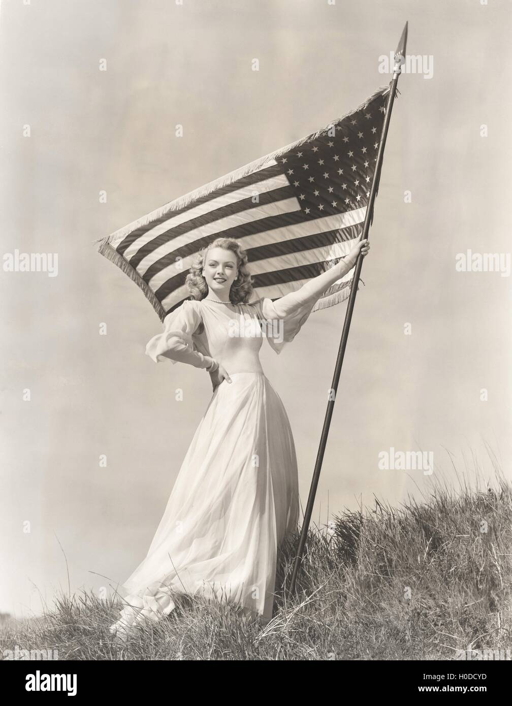 Proud woman in gown holding American flag on hill - Stock Image
