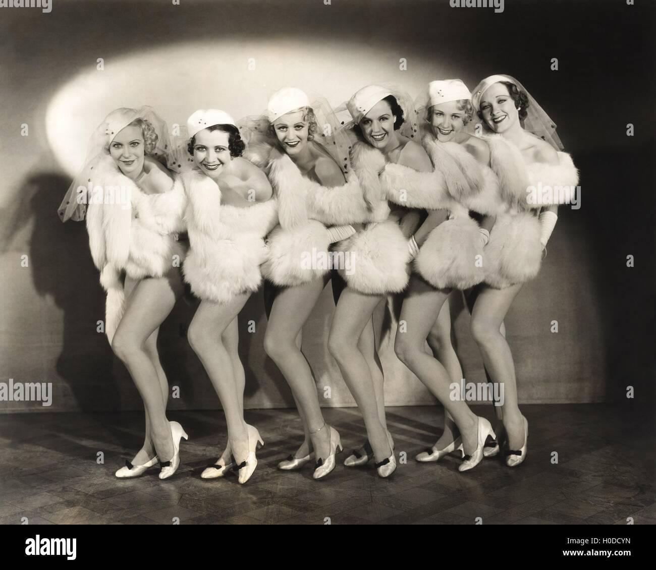 Line of chorus girls in white fur - Stock Image