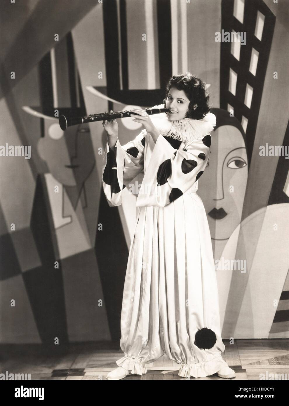 Woman in clown costume playing clarinet - Stock Image