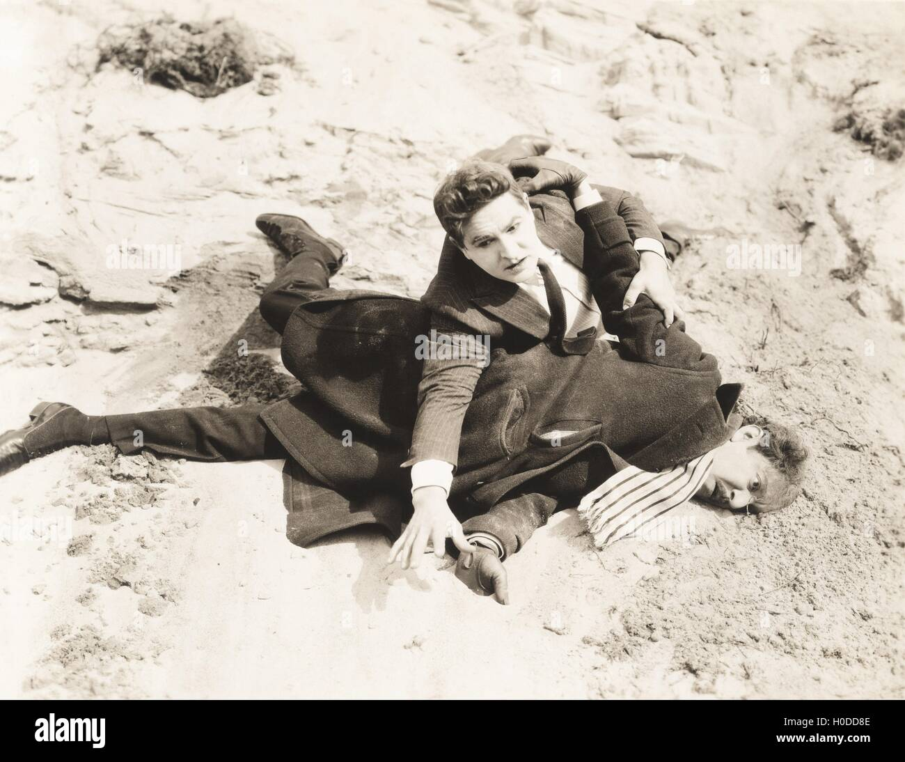 Man pinned to the ground during fight - Stock Image