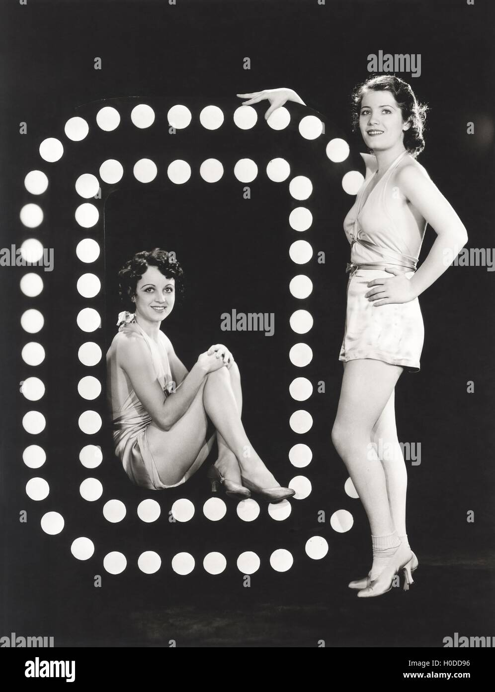 Two models posing by large letter O - Stock Image
