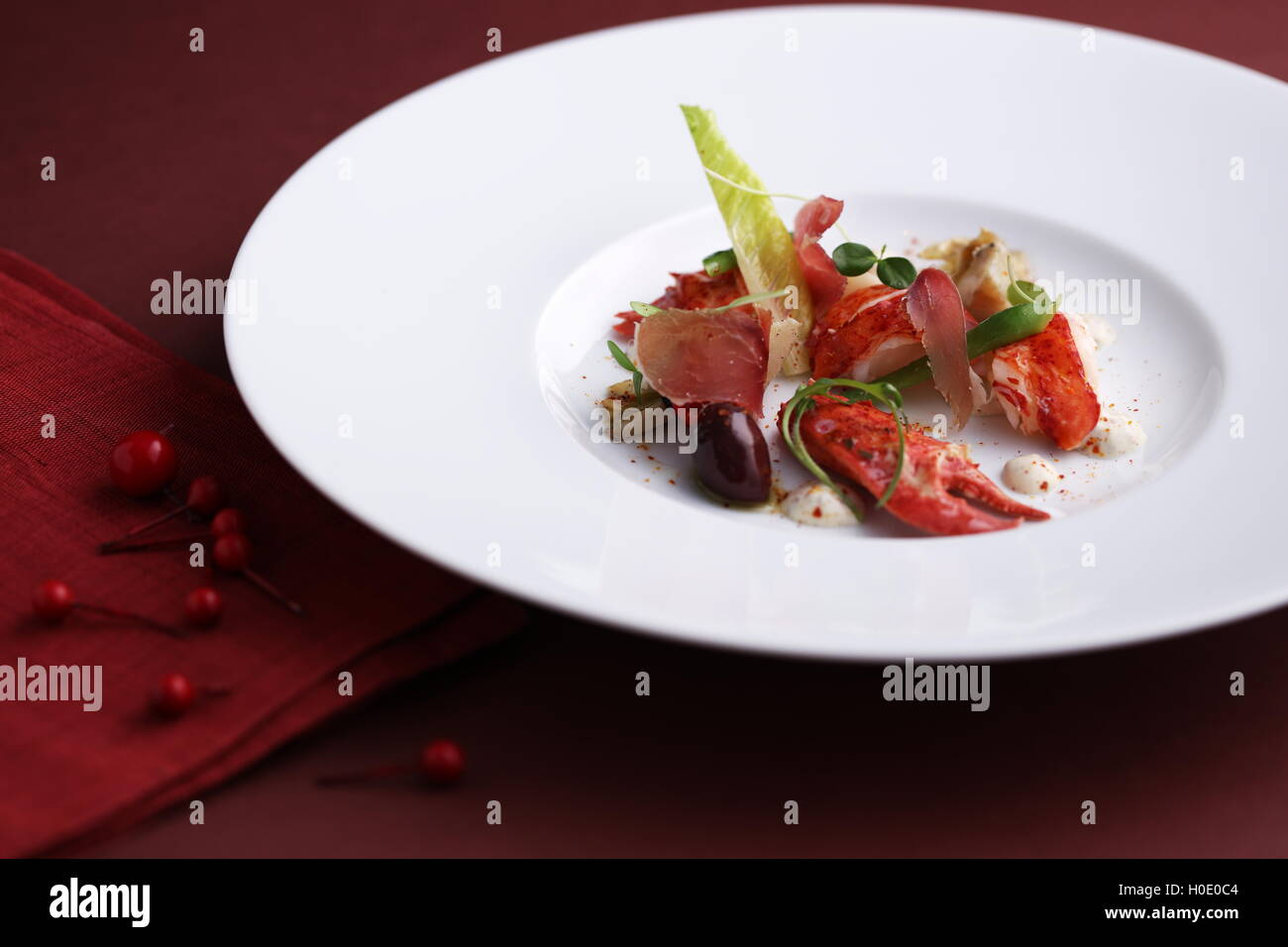 Atlantic blue lobster salad marinated on white plate in black background - Stock Image