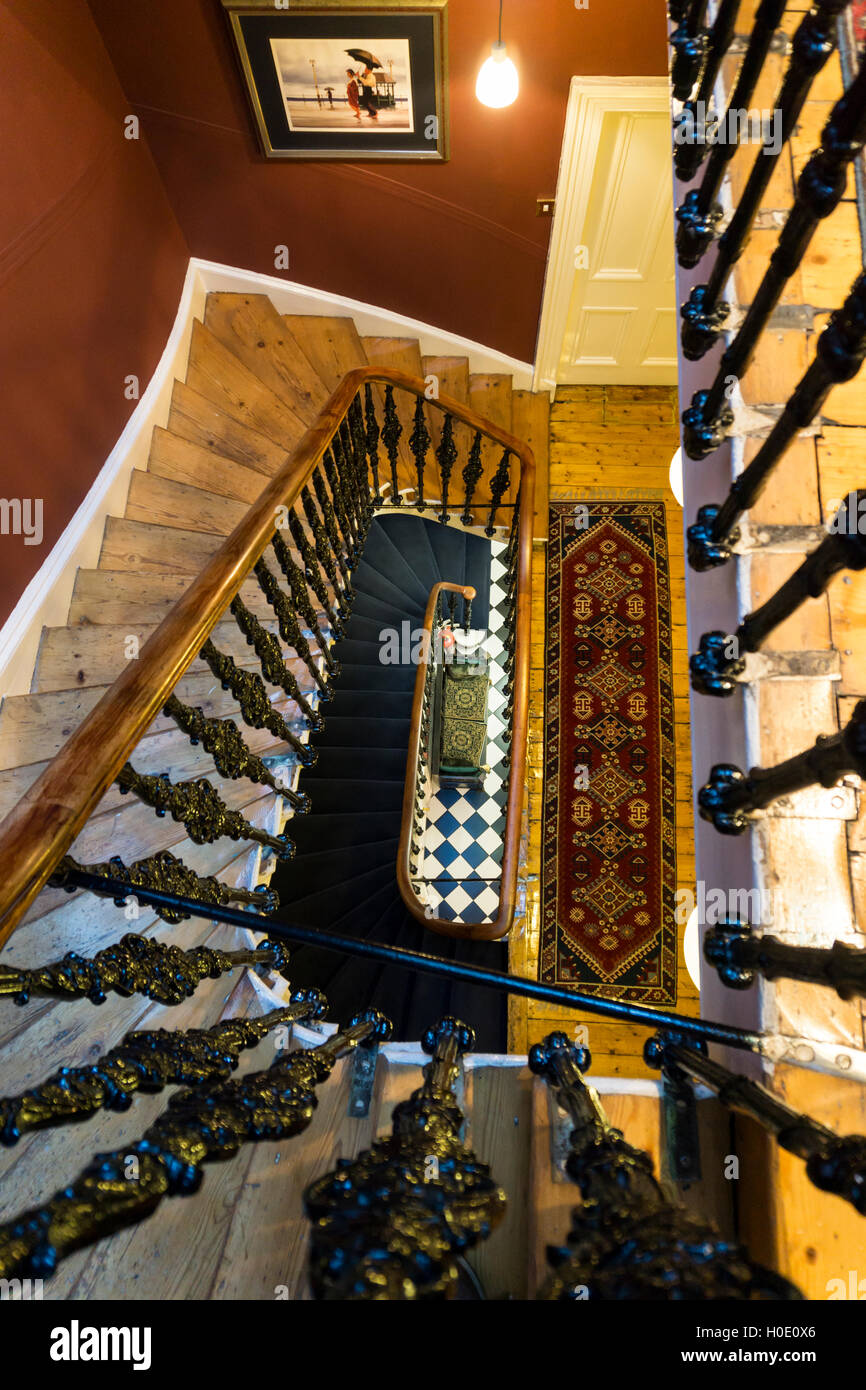 A vertiginous view down the staircase from the top floor of a tall old house. - Stock Image